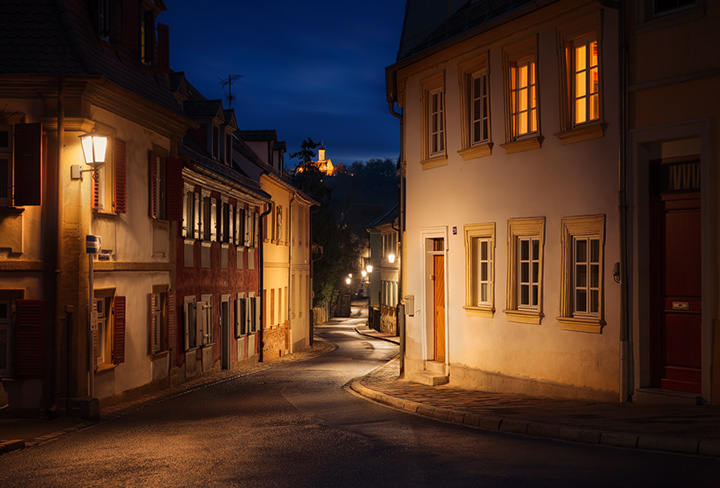 A dark street in historic Bamberg, lit by stree lights