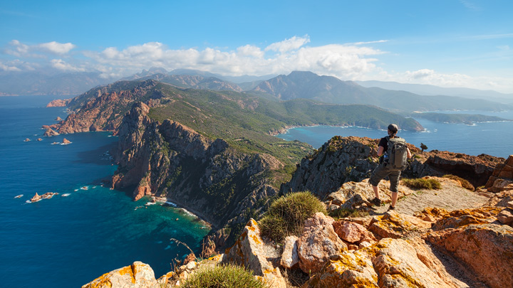 A man standing at the edge of a steep cliff looking towards the Corsica Mountains