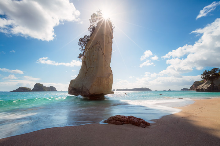 The sun behind sail rock at Cathedral Cove
