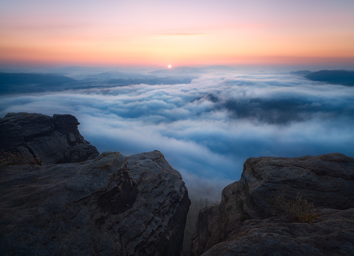 View across a sea of clouds towards the rising sun