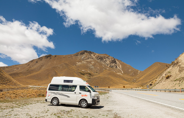 A Campervan at Lindis Pass under a blue sky