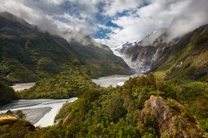 Franz Josef Glacier with the rainforest in the foreground on a sunny day