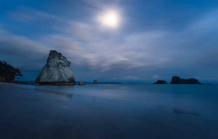 A full moon glimpses through the clouds at Cathedral Cove