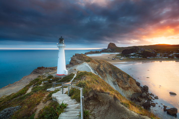 View along the Castlepoint coast during sunset, with a white Lighthouse on the cliffs