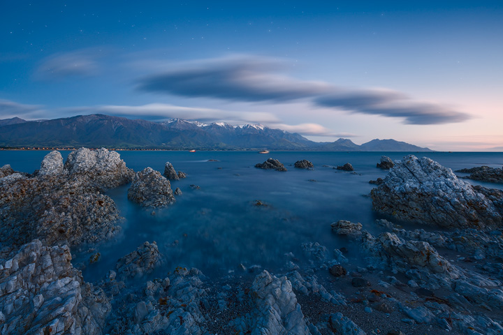 Snow capped mountains under a starry sky with calm sea in front