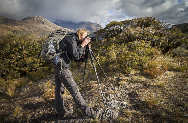 A photographer in front of some mountain landscape in New Zealand