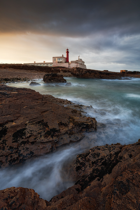 A rocky coast and a lighthouse during sunrise