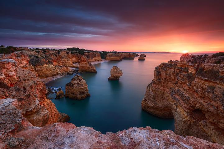 Colorful sunrise over the cliffs at Praia da Marinha