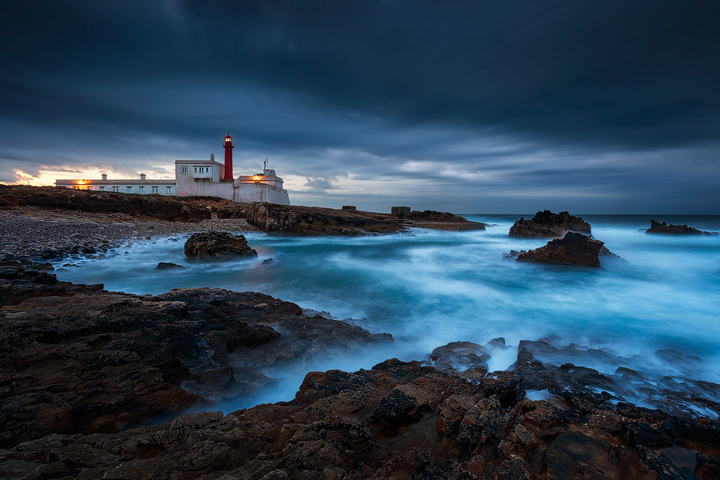 A lighthouse facing the stormy sea on a rocky shore