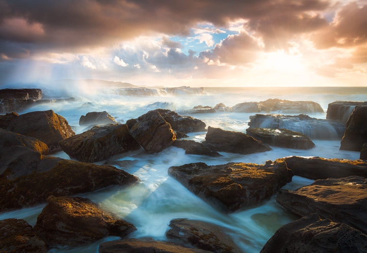 Waves breaking on some rocks during a spectacular sunrise