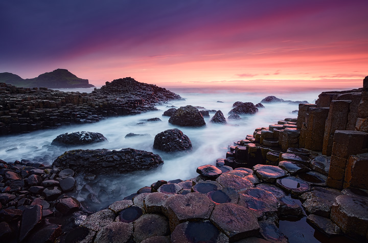 Hexagonal rocks, foglike water and a colorful sky.