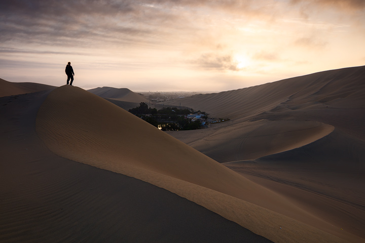 A man looking down on Huacachina from a huge dune