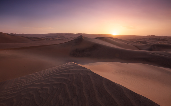 The sun sets behind the Huacachina desert