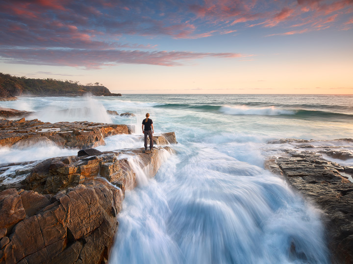 A man standing on the rocks of the Noosa coast, surrounded by waves