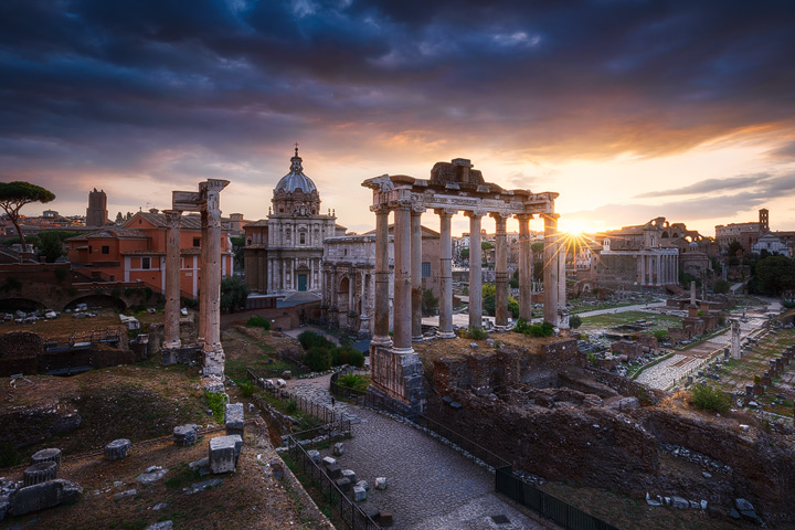 The sun rises behind the ruins of the Forum Romanum
