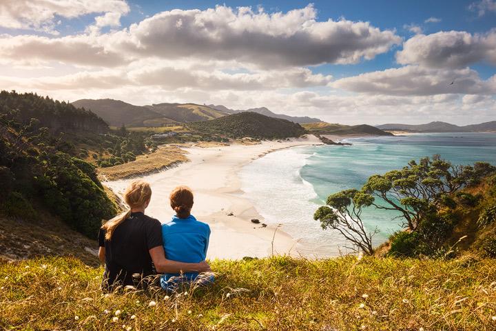 A joung couple overlooking Ocean Beach in New Zealand