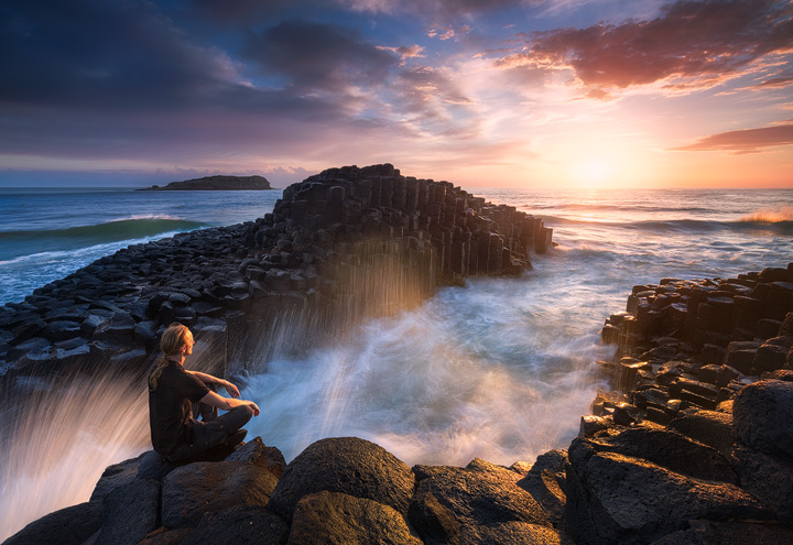A person meditating on the rocks of Fingal head