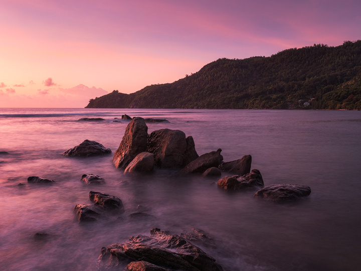 The coast of Mahe with its typical granite rocks during a colorful sunrise