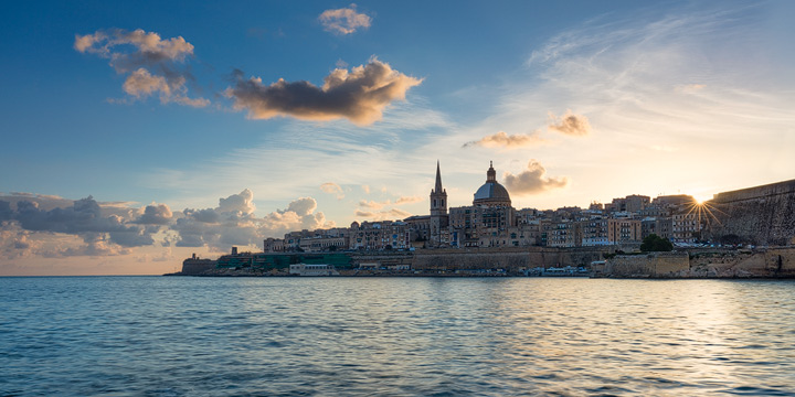The sun peeks over the roofs of Valletta
