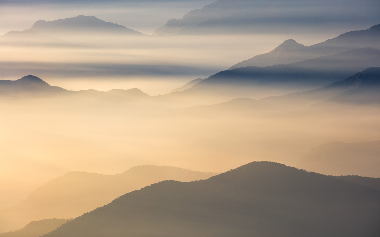Mountains emerging from layers of fog and low clouds