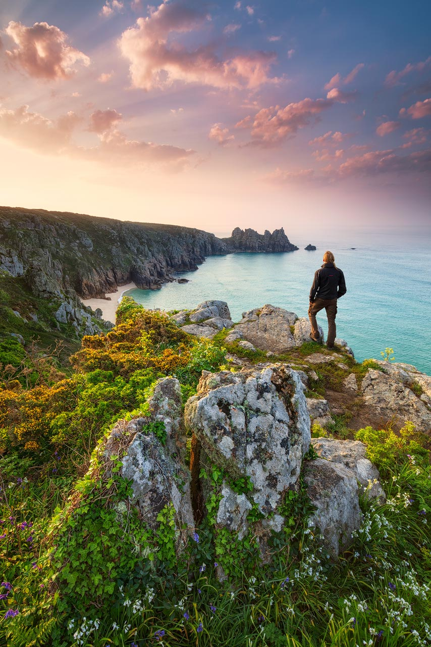 Beautiful sunrise near Porthcurno in Cornwall with spring flowers blooming on the cliffs.