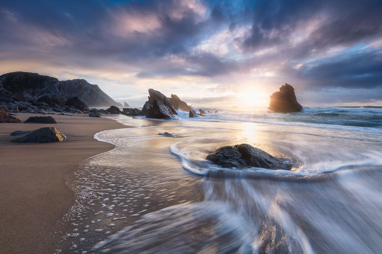 Intense sunset at the rocky Praia da Adraga beach