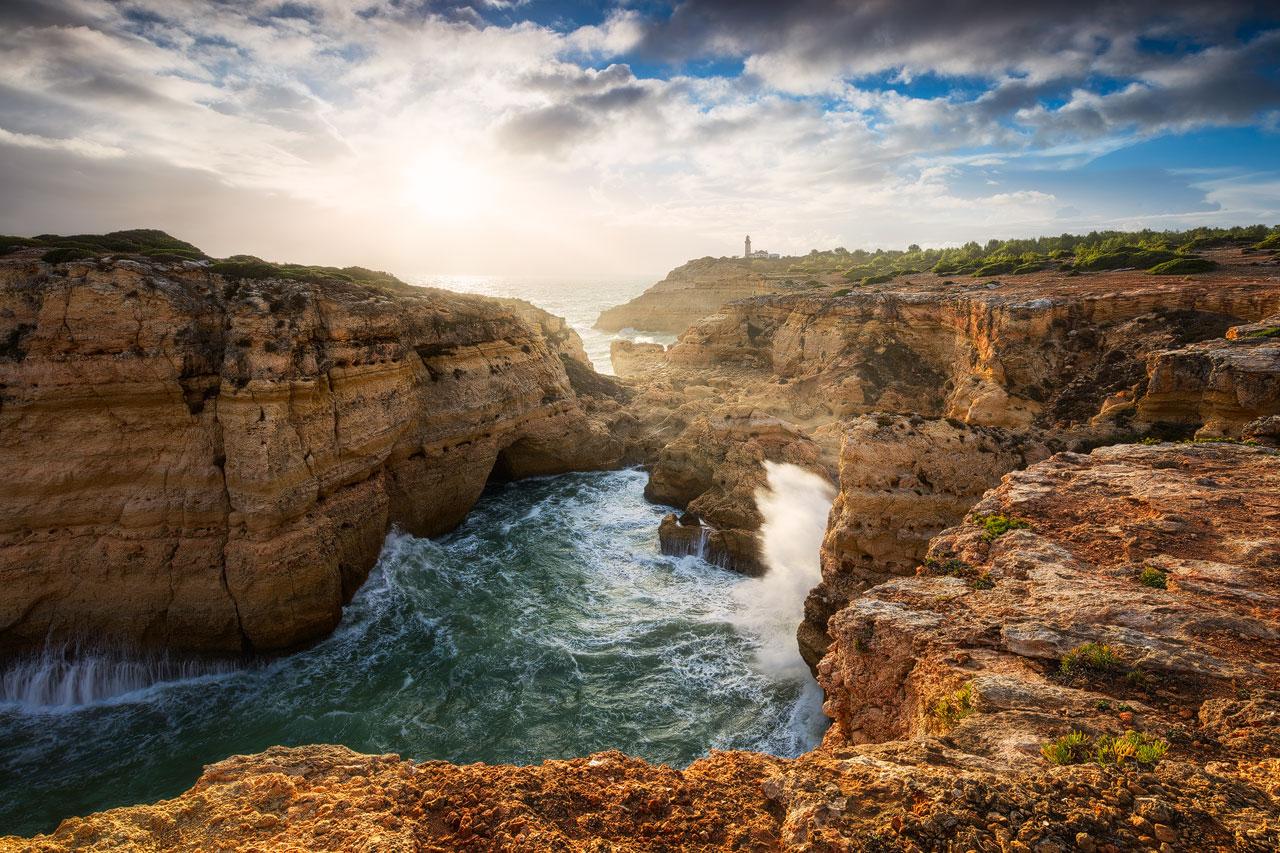 Enormous waves crashing on the rocks near Alfanzina Lighthouse at the Algarve