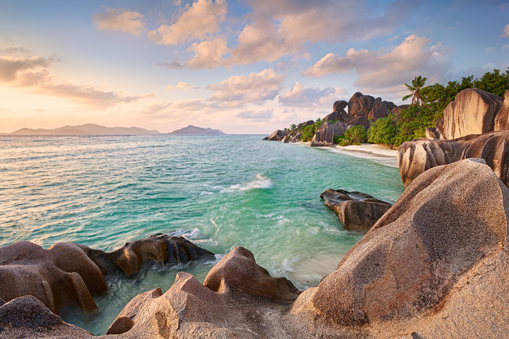 A beautiful tropical beach lined by huge rocks and palm trees on La Digue.