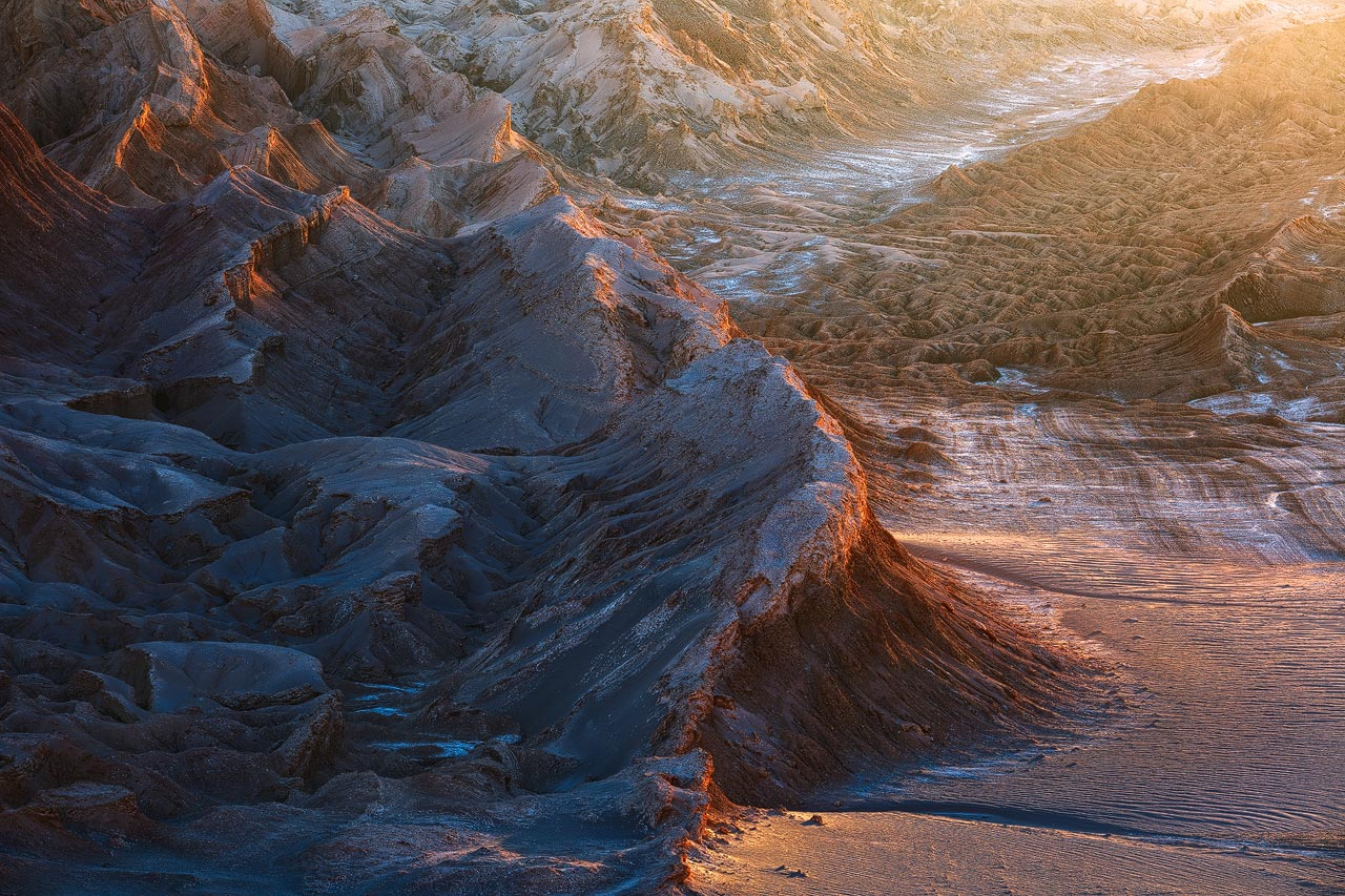 The sun bathes the rock formations of Valle de la Luna in Chile in golden light during sunset.