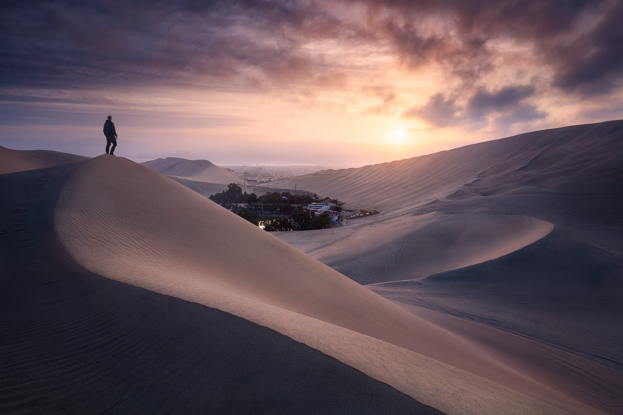 The desert town Huacachina near Ica with the surrounding dunes during sunrise.