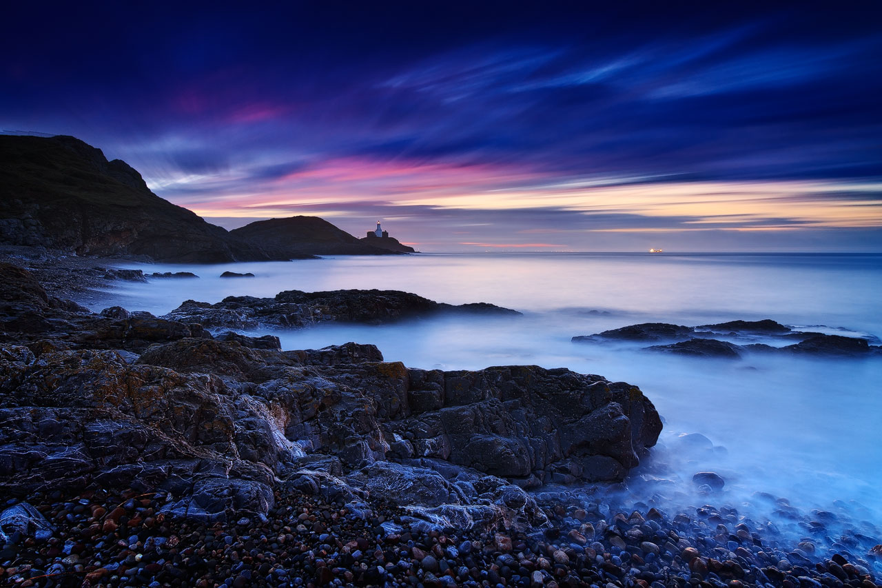 Bracelet Bay with Mumbles Lighthouse before sunrise.