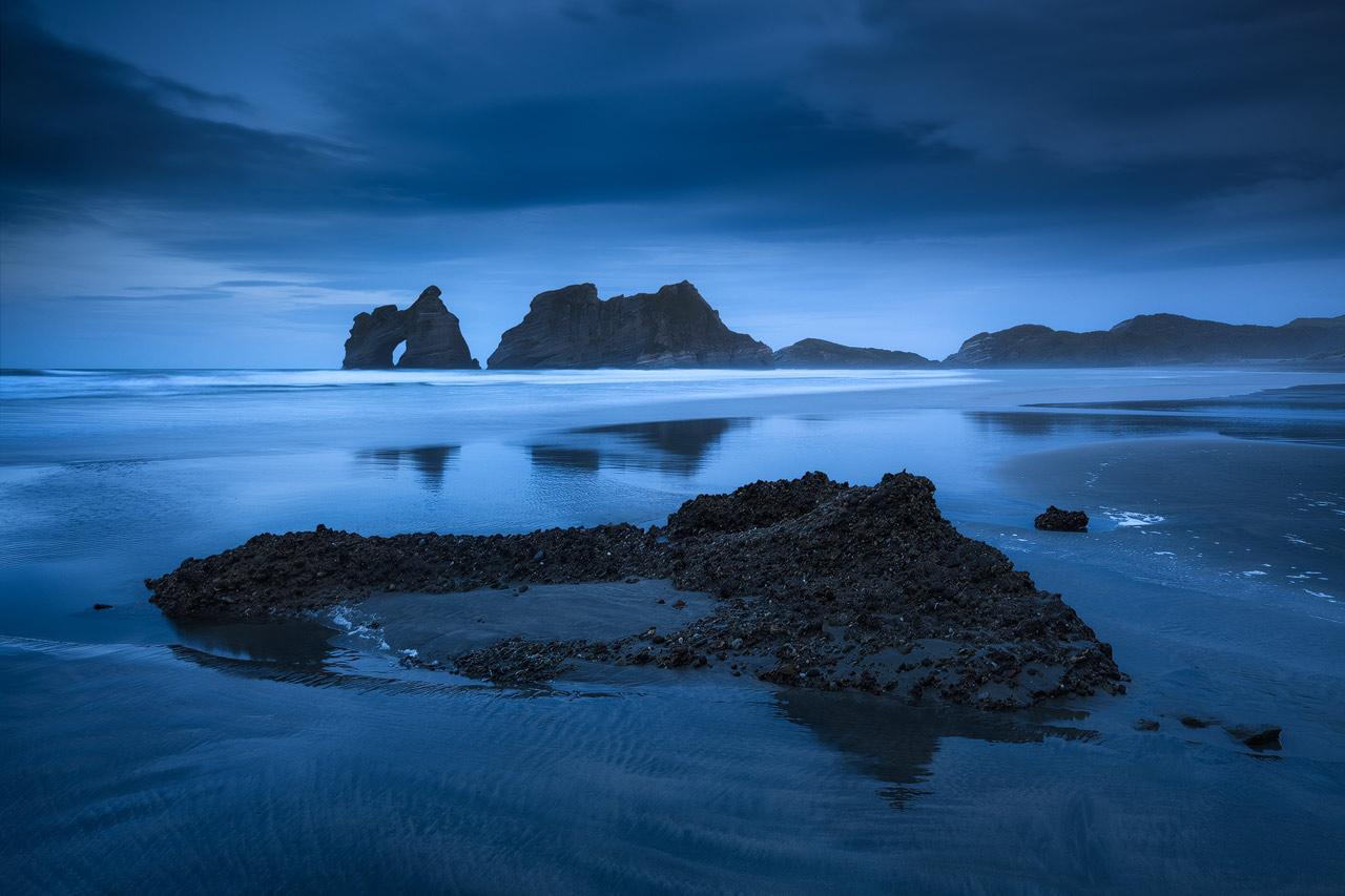 The sea stacks at Wharariki beach under a dark blue twilight sky