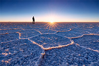 Person standing on the endless salt flats of Salar de Uyuni during sunset